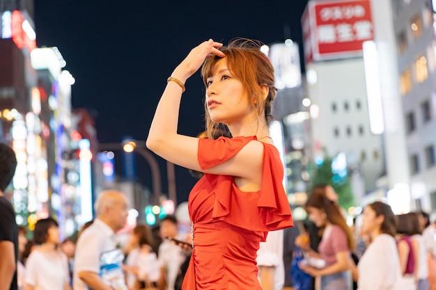 日本の女性が東京の通りで華やかな赤いドレスでポーズ