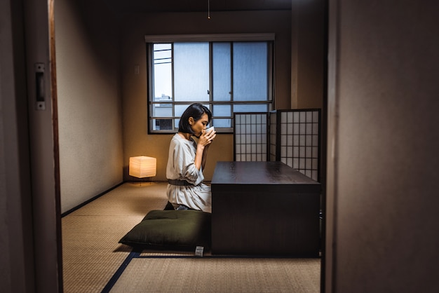 Japanese woman sits at home and drinks tea