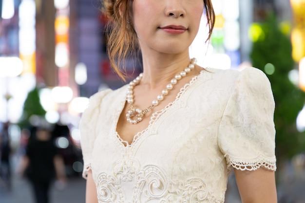 東京の通りで華やかなネックレスを持つ日本人女性