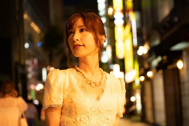 東京の通りで華やかな白いドレスの日本人女性