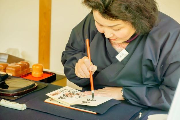 노트북에 검은 잉크에서 일본어 텍스트를 작성하는 중국 붓을 들고 일본 여성