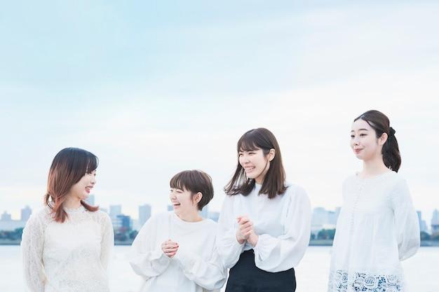 白いトップスを着て笑顔で話す日本人女性