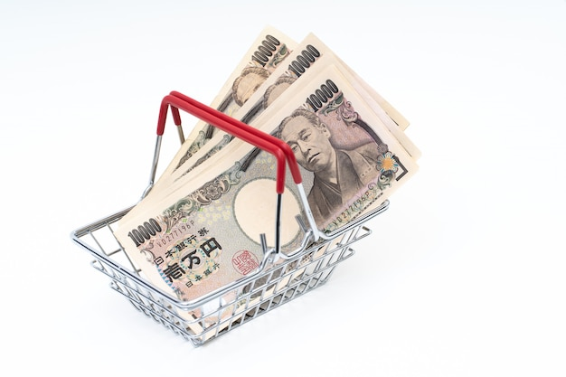 Japanese yen banknote in shopping basket on white background