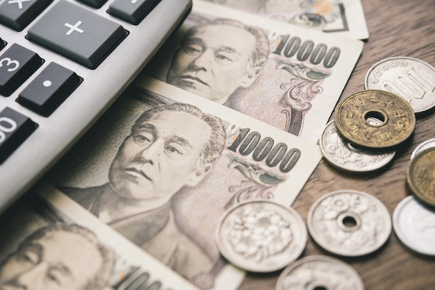 Japanese yen money bills and coins with calculator on the table