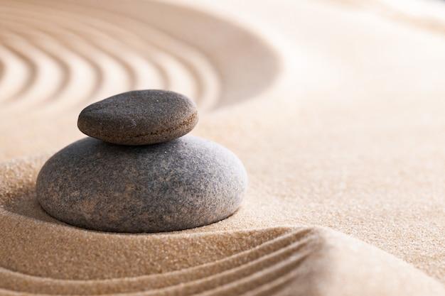 掻き集められた砂の石が付いている日本の禅の庭