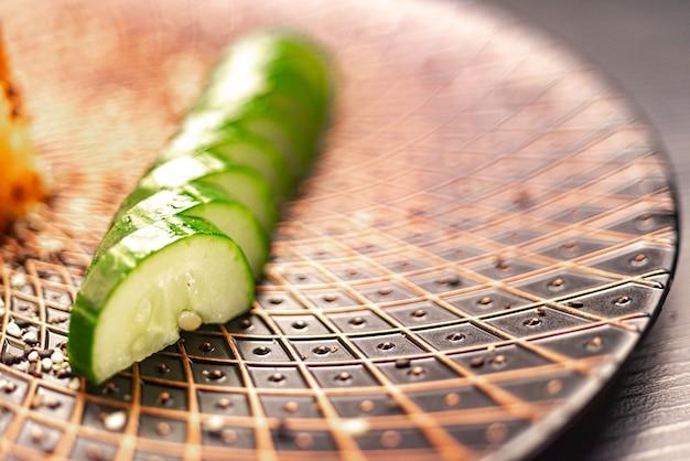 Японская кухня. салат из огурцов, нарезанный дольками, подается на тарелке с васаби.
