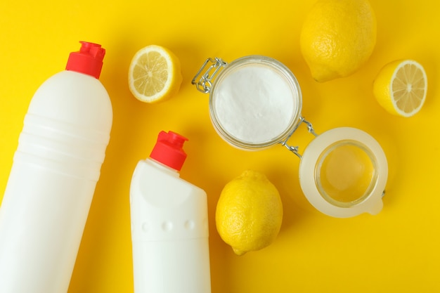 Jar of acid powder, lemons and detergents on yellow isolated background
