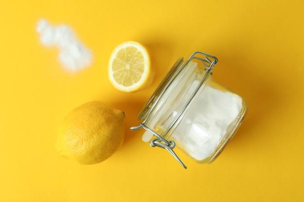 Jar of acid powder and lemons on yellow isolated background