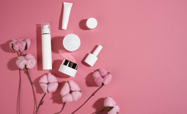 분홍색 배경에 화장품을 위한 항아리와 빈 흰색 플라스틱 튜브. 크림, 젤, 혈청, 광고 및 제품 판촉용 포장, 평면도, 복사 공간