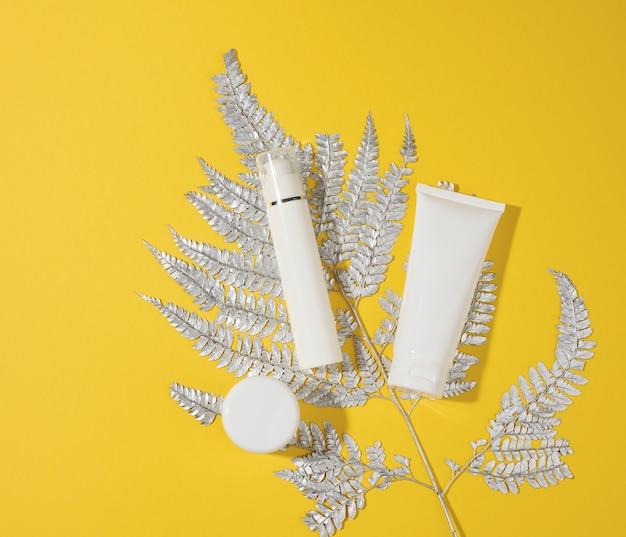 Баночка и пустые белые пластиковые тубы для косметики на желтом фоне. упаковка для крема, геля, сыворотки, рекламы и продвижения продукции, вид сверху