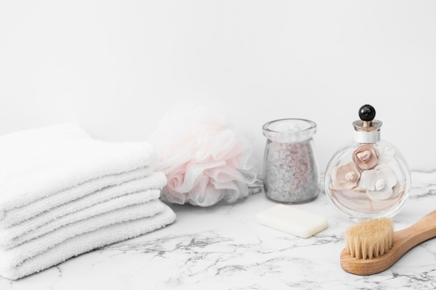 Jar of bath salt; towels; sponge; brush; soap and perfume bottle on marble surface