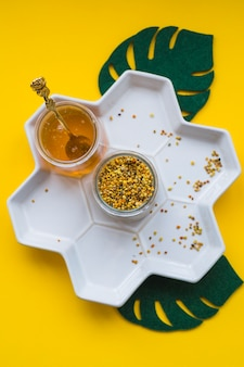 Jar of bee pollens and honey on white tray over the yellow background