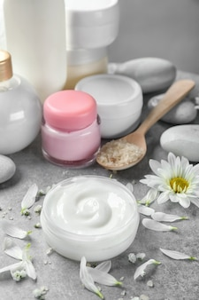 Jar of body cream and flower petals on table