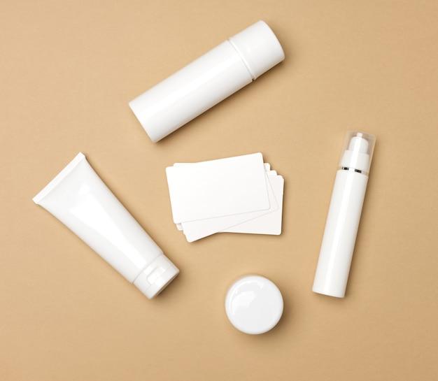 ベージュの背景に化粧品用の瓶、ボトル、空の白いプラスチックチューブ。クリーム、ジェル、美容液、広告、製品プロモーション、モックアップ、上面図のパッケージ
