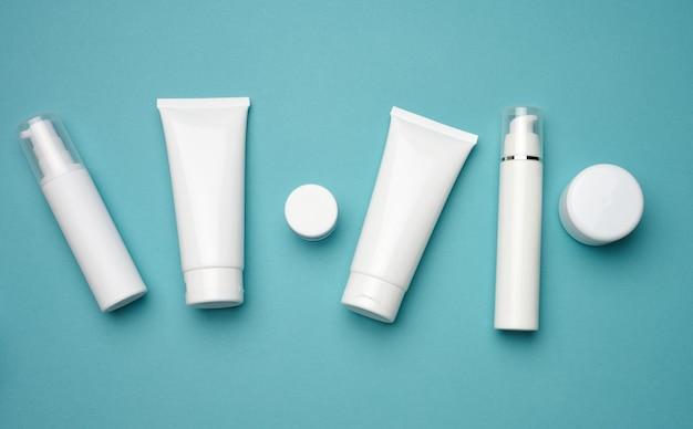 青い背景の化粧品用の瓶、ボトル、空の白いプラスチックチューブ。クリーム、ジェル、美容液、広告、製品プロモーションのパッケージ、モックアップ