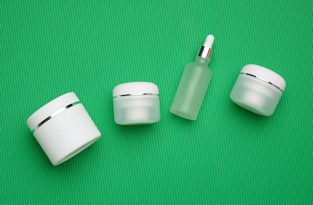 녹색 배경에 화장품을 위한 항아리, 병, 빈 흰색 플라스틱 튜브. 크림, 젤, 혈청, 광고 및 제품 판촉용 포장, 모형