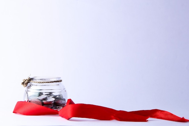 A jar containing silver coins tied with small ropes and decorated with red ribbons