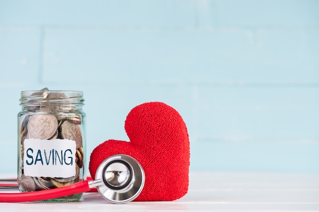 A jar contains coins with stethoscope and red heart on wooden background.