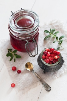 Jar of cowberry jam with a spoon and berries