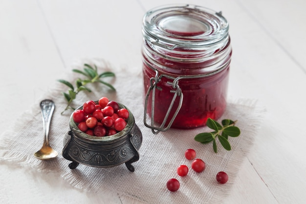 Jar of cowberry jam with a spoon