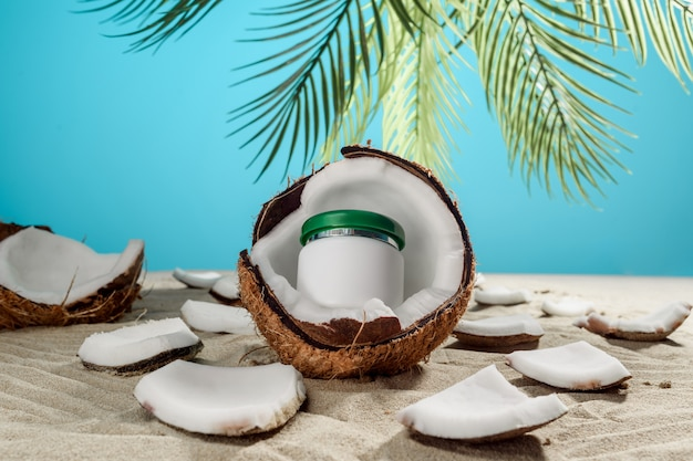 A jar of cream is inside the coconut. natural cosmetic.