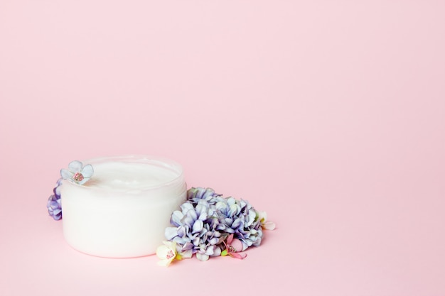 A jar of cream with flowers on pink