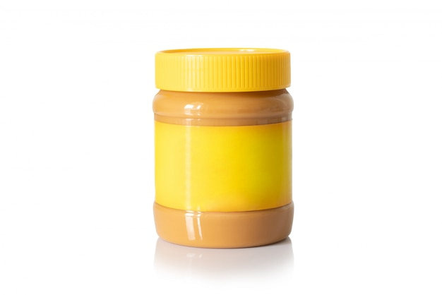 Jar of creamy peanut butter with yellow cap and yellow label isolated on white