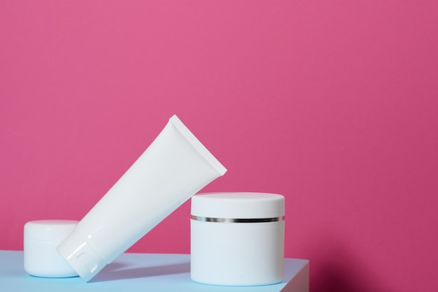 Jar and empty white plastic tubes for cosmetics on a pink background. packaging for cream, gel, serum, advertising and product promotion, mock up