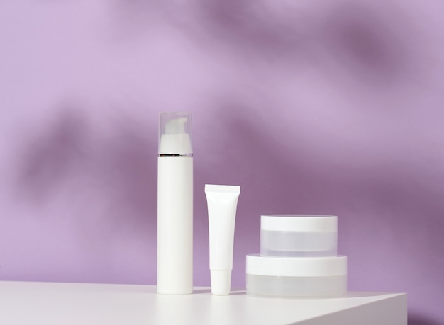 Jar and empty white plastic tubes for cosmetics on a purple background. packaging for cream, gel, serum, advertising and product promotion, mock up