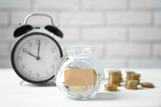 Jar filled with coins and alarm clock on background