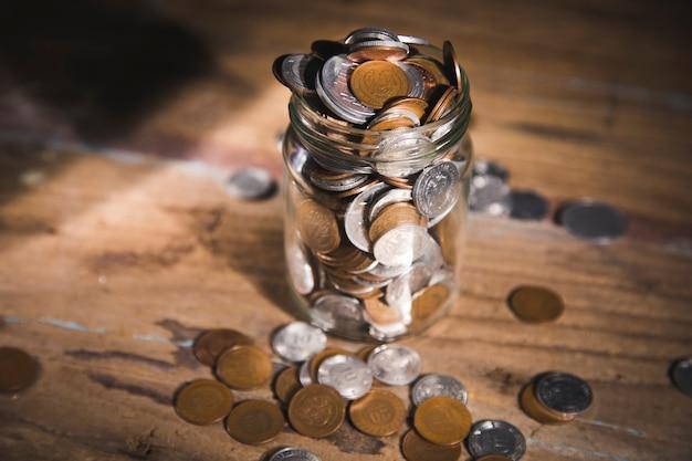 Банка с монетами на деревянном столе