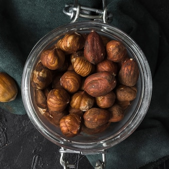 Jar filled with dry hazelnuts close-up