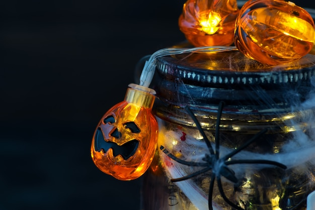 Jar filled with orange string lights in spooky room full in a black jar with a web and a spider