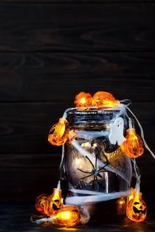 Jar filled with orange string lights in spooky room full of black webs.