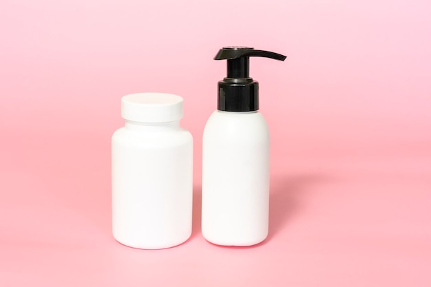 ビタミンや栄養補助食品の瓶とポンプボトルのモックアップピンクの背景。ナチュラルスキンケア美容製品。ブランディングとパッケージングのプレゼンテーション。
