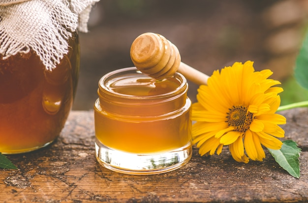 Jar of fresh honey, wooden honey dipper and honeycombs in field of wildflowers. honey  and  wooden drizzler on table near field of wildflowers