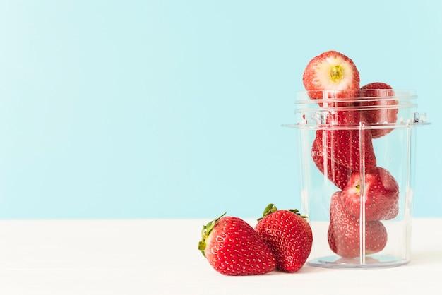 Jar of fresh red strawberries on table top