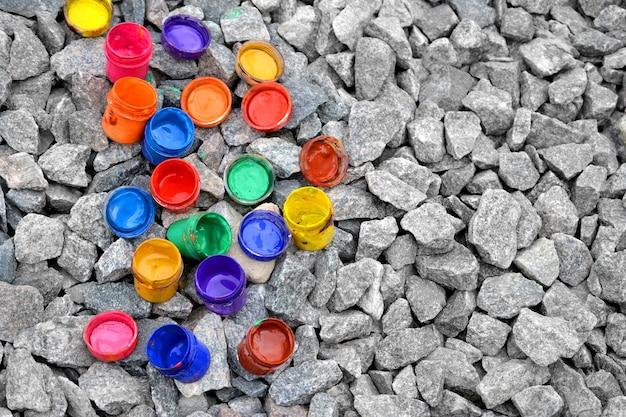 灰色の石にさまざまな色の絵の具の下からの瓶、上からの眺め