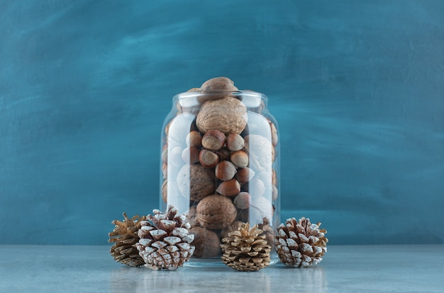 A jar full of various nuts next to pine cones on marble surface