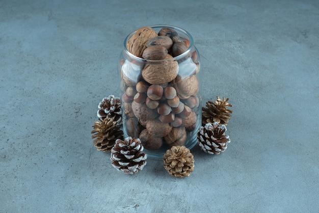 Un vaso pieno di vari dadi accanto alle pigne sulla superficie di marmo