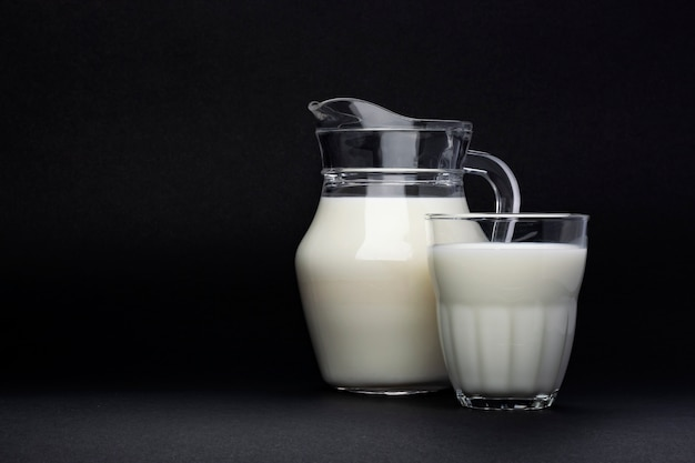 Jar and glass of milk isolated on black with copy space for text, dairy product concept