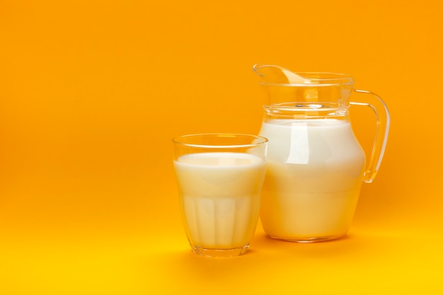 Jar and glass of milk isolated on yellow background with copy space for text, dairy product concept