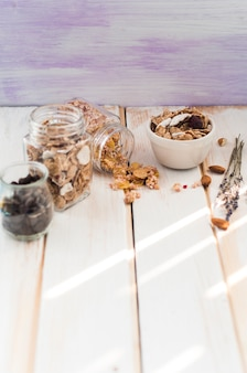 Jar of granola; cornflakes and chocolate chips near dry fruits on wooden surface
