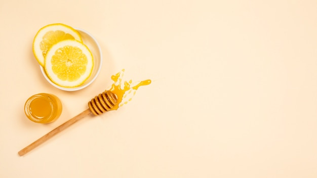 Jar of healthy honey and lemon slice with honey dipper on plain surface
