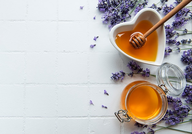 Jar and heartshaped bowlwith honey and fresh lavender flowers on a white tile background