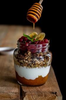 Jar of homemade granola with yogurt, homemade apricot jam and raspberries on dark