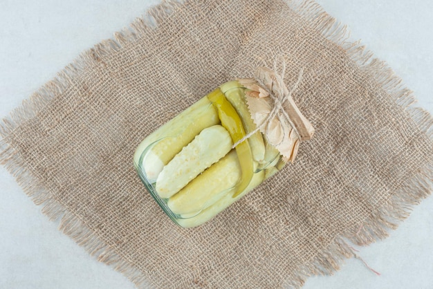 A jar of homemade pickled cucumbers on burlap.