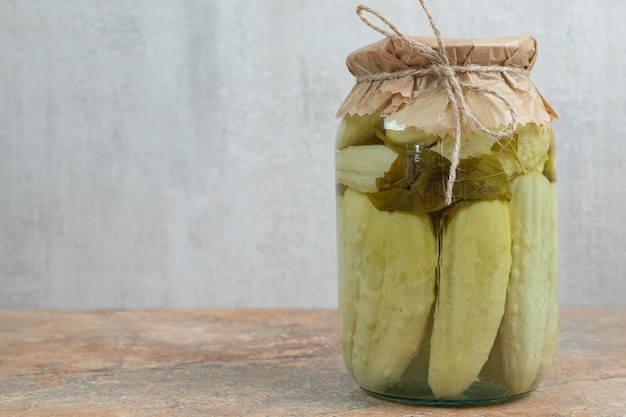 A jar of homemade pickled cucumbers on marble table