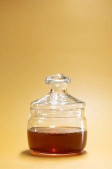 Jar of honey on a bright yellow background in an advertising food photo style. vertical