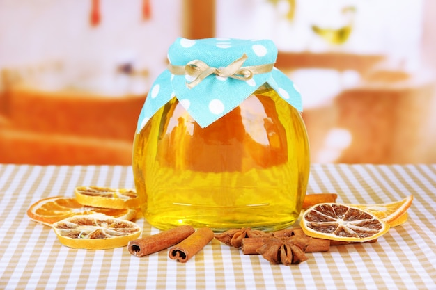 Jar of honey and dried lemon slices on bright surface